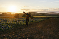 Spain, Catalunya, Girona, woman hiking on field path at sunrise - EBSF001180