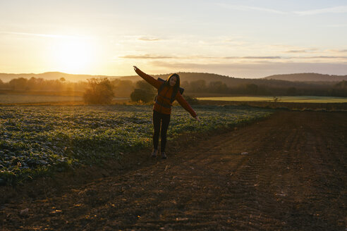 Spain, Catalunya, Girona, woman hiking on field path at sunrise - EBSF001180