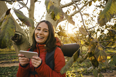 Spain, Catalunya, Girona, portrait of happy female hiker with cell phone at a tree - EBSF001183