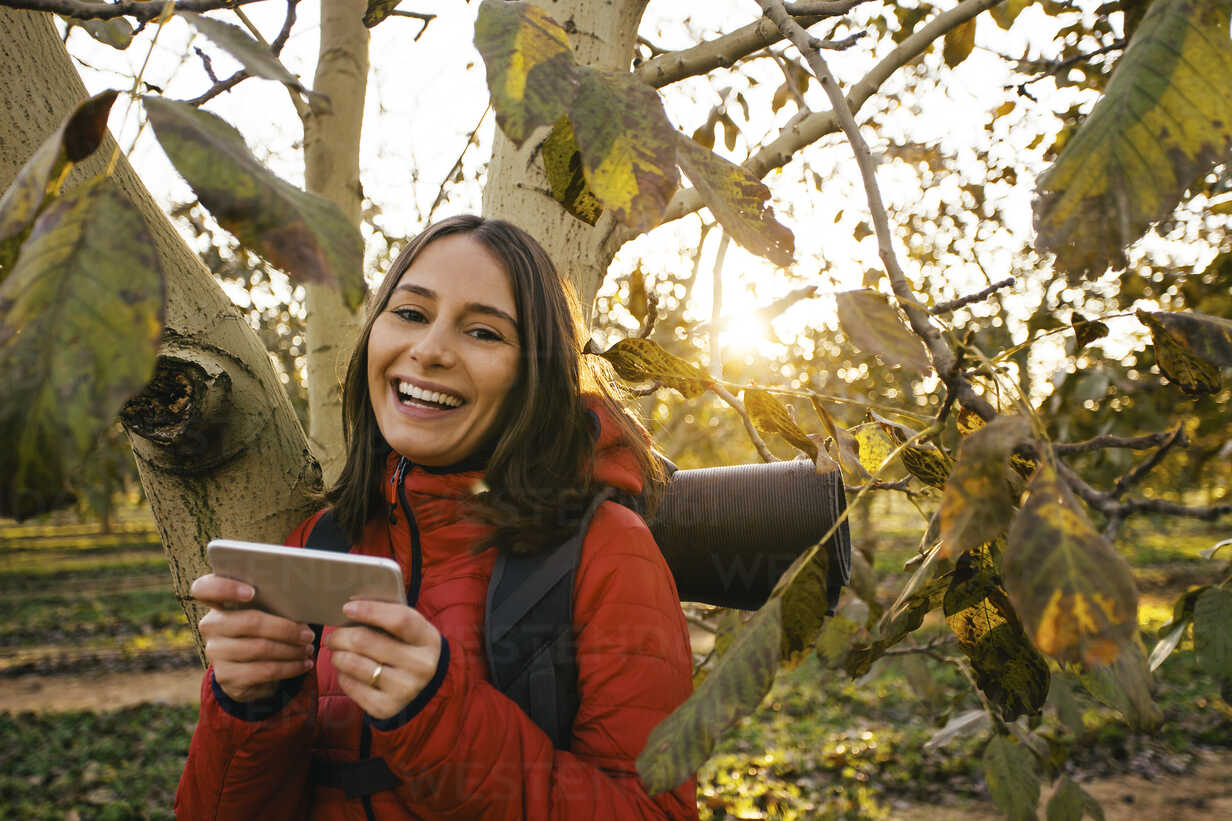 Spain, Catalunya, Girona, portrait of happy female hiker with cell phone at a tree - EBSF001183 - Bonninstudio/Westend61