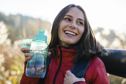 Spain, Catalunya, Girona, portrait of happy female hiker holding bottle of water - EBSF001186