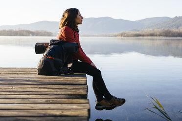 Spain, Catalunya, Girona, female hiker resting on jetty at a lake enjoying the nature - EBSF001189