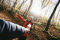 Spain, Catalunya, Girona, smiling woman in the woods holding man's hand - EBSF001204