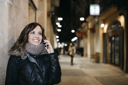 Spain, Reus, portrait of smiling young woman telephoning with smartphone at night - JRFF000249