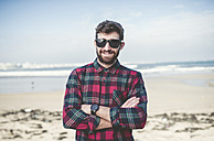 Spain, La Coruna, portrait of smiling hipster with sunglasses standing on the beach - RAEF000726