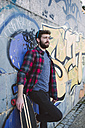 Spain, La Coruna, portrait of hipster leaning against wall with his longboard - RAEF000735
