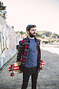 Spain, La Coruna, portrait of hipster with his longboard - RAEF000738