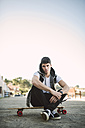 Spain, La Coruna, portrait of serious looking young man sitting on his longboard - RAEF000744