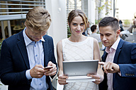 Three young businesspeople with digital tablet and cell phone outdoors - WESTF021601