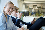 Portrait of confident businesswoman with colleague in office - WESTF021619