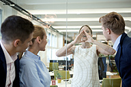Businesswoman behind glass wall shouting at colleagues in office - WESTF021622