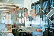 Successful business team behind glass wall in office looking at folder - WESTF021631