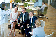 Businesswoman talking to expectant businessspeople in office - WESTF021637