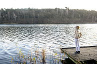 Blond woman standing on wooden boardwalk looking at a lake - BFRF001698