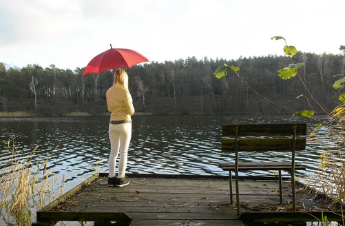 Back view of blond woman standing on wooden boardwalk with red umbrella looking at a lake - BFRF001701