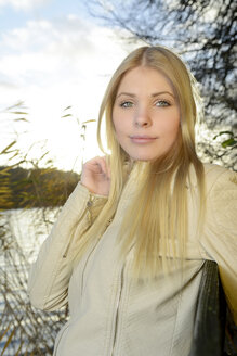 Portrait of young blond woman in front of a lake - BFRF001707