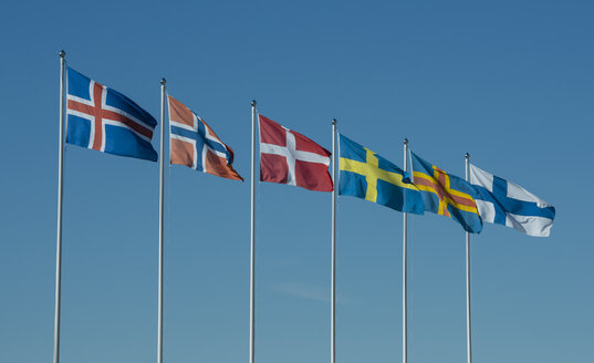 Row of Scandinavian national flags in front of blue sky - JBF000260