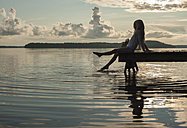 Finland, Karelia, Uukuniemi, Lake Pyhäjärvi, girl sitting on jetty splashing with her feet in the water - JBF000263