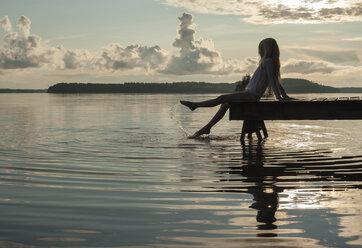 Finland, Karelia, Uukuniemi, Lake Pyhäjärvi, girl sitting on jetty splashing with her feet in the water - JBF000263