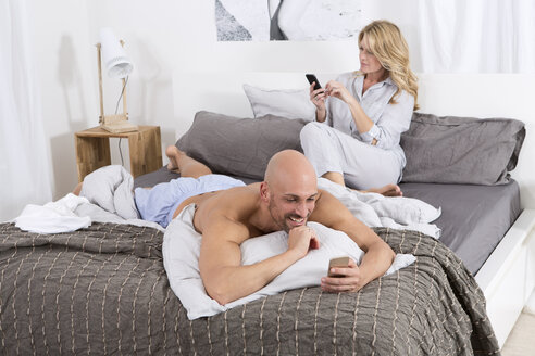 Mature couple in bedroom using their mobile phones - MAEF011076
