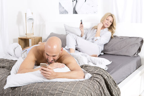 Mature couple in bedroom using their mobile phones - MAEF011079