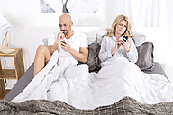 Mature couple sitting in bed using smartphones - MAEF011082