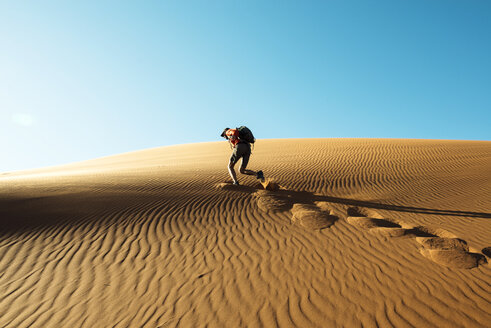 Namibia, Namib Desert, Sossusvlei, Man climbing a dune at sunset - GEMF000549