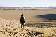Namibia, Namib Desert, Sossusvlei, Woman with hat and backpack looking at the horizon - GEMF000552