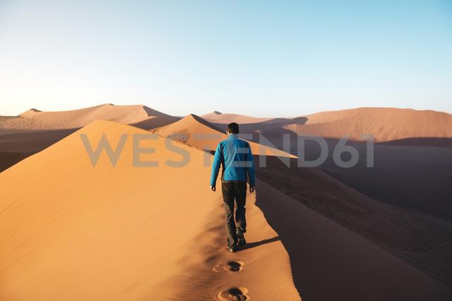 Namibia, Namib Desert, Sossusvlei, Man walking on the top of the famous Dune 45 at sunrise - GEMF000555