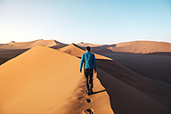 Namibia, Namib Desert, Sossusvlei, Man walking on the top of the famous Dune 45 at sunrise - GEMF000555