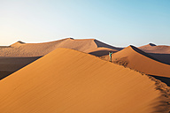 Namibia, Namib Desert, Sossusvlei. Woman with raised arms on Dune 45 at sunrise - GEMF000558