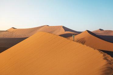 Namibia, Namib Desert, Sossusvlei. Woman with raised arms on Dune 45 at sunrise - GEMF000558