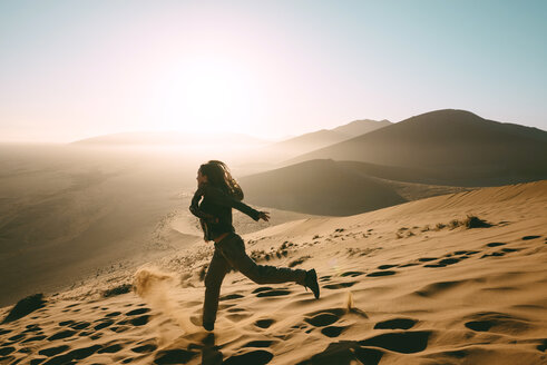 Namibia, Namib Desert, Sossusvlei, Woman running down the Dune 45 at sunrise - GEMF000561
