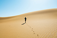 Namibia, Namib Desert, Sossusvlei, Man walking through the dunes - GEMF000564