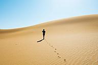Namibia, Namib Desert, Sossusvlei, Man walking through the dunes - GEMF000564