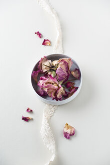 Bowl of dried rose blossoms and lace on white ground - MYF001273