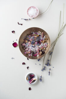 Bowl of bath salts with dried rose petals and lavender blossoms - MYF001276