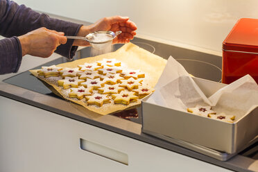 Woman's hands sprinkling Christmas cookies with icing sugar - WDF003484