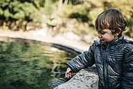 Toddler holding his hand into a pool - JRFF000258