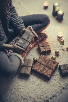 Woman sitting with Christmas presents on the carpet - JPF000085