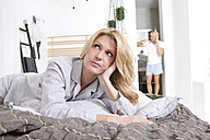 Annoyed woman lying on bed while man is on the phone in background - MAEF011087
