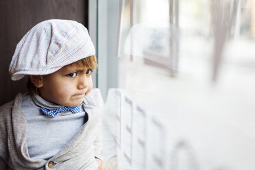 Portrait of angry little boy with cap looking through window - VABF000015
