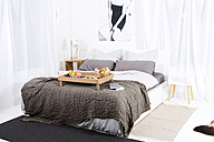 Books and breakfast on empty bed in bedroom - MAEF011116