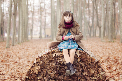 Young girl sitting on autum leaves ball - XCF000052