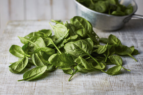 Fresh spinach leaves on wood, colander - KSWF001714