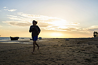 Spain, Puerto Real, woman jogging on the beach at sunset - KIJF000043