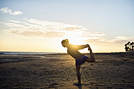 Spain, Puerto Real, silhouette of young woman doing yoga on the beach at sunset - KIJF000049