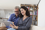 Smiling couple at home on couch using digital tablet - RBF003637