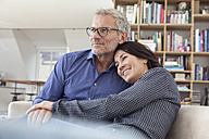 Smiling mature couple cuddling at home - RBF003640