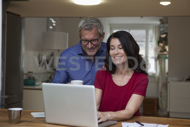 Smiling couple at home using laptop at table - RBF003646